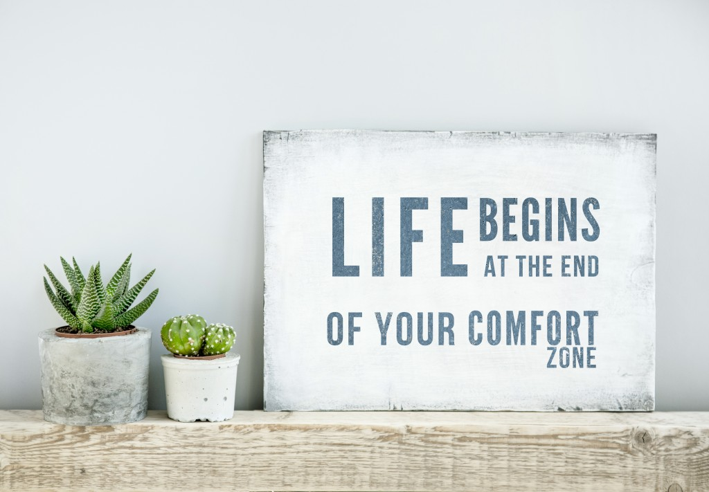 motivational poster quote LIFE BEGINS AT THE END OF COMFORT ZONE. scandinavian or american style room interior.
