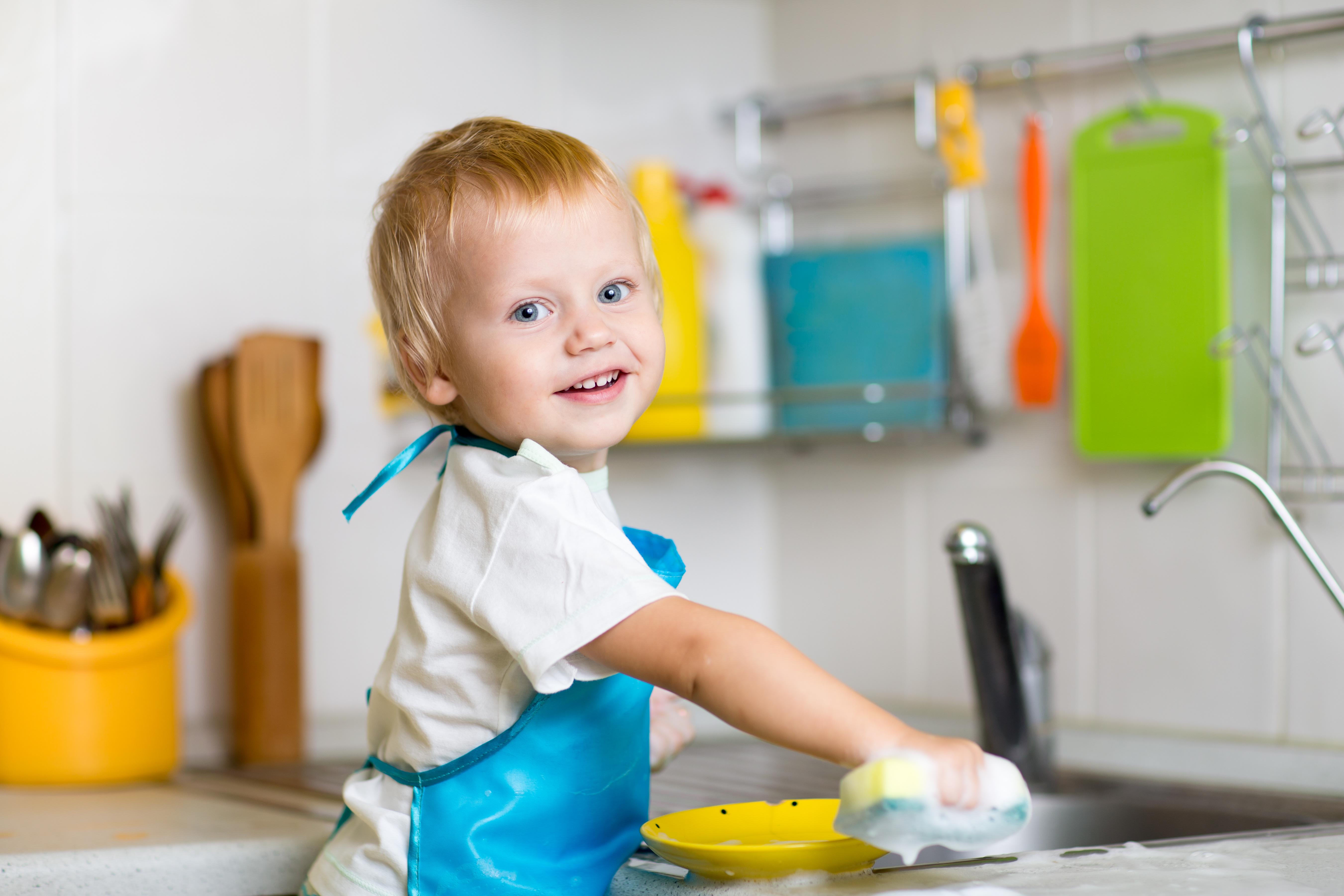 Toddler child washing dishes in kitchen. Little boy having ...